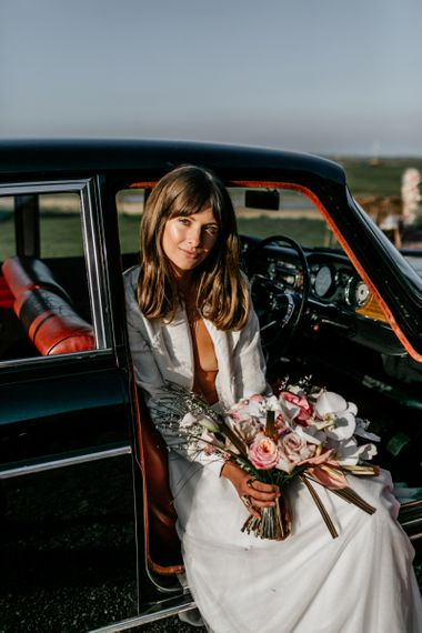 Boho Bride with Sweeping Fringe Sitting in a Wedding Car Holding a Bouquet