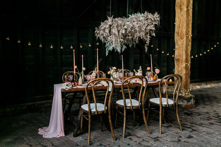 Wooden Table Setting with Flower Cloud Installation and Coloured Table Ware and Flower Decor
