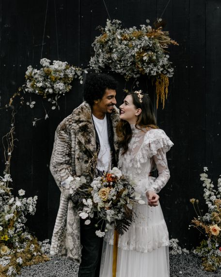 Bride in Katya Katya Wedding Dress and Groom in Faux Fur Coat Smiling at the Dried Flower Altar