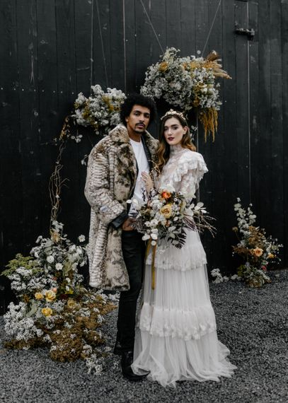 Bride in Tired Wedding Dress with Dried Flower Bouquet and Groom in Faux Fur Coat