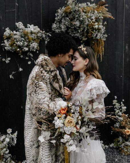 Intimate Portrait of Bride and Groom Standing Next to Their Dried Flower Arrangement