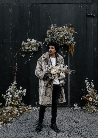 Stylish Groom in White T-Shirt and Faux Fur Overcoat Holding a Dried Flower Bouquet