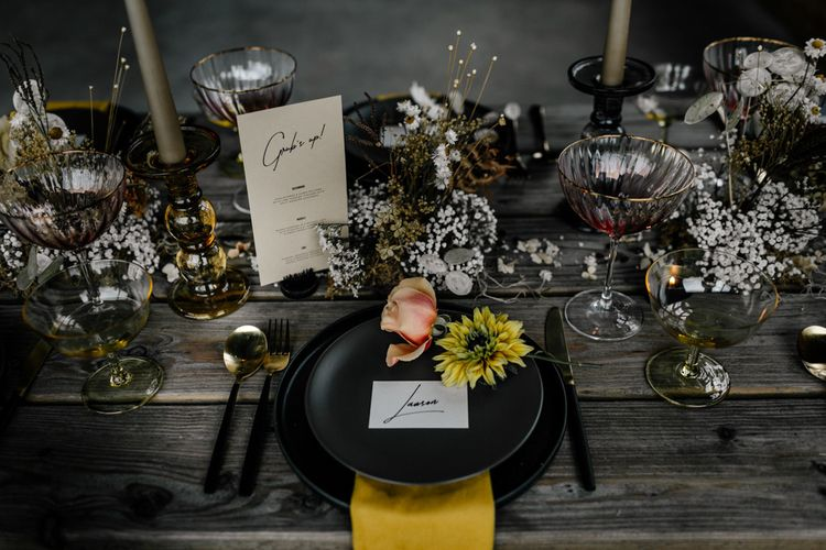 Place Setting with Black Table Ware, Yellow Napkin, Individual Flowers Stems and Modern Name Place Card