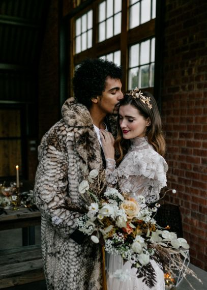Groom in Faux Fur Coat Kissing His Bride in a High Neck Wedding Dress