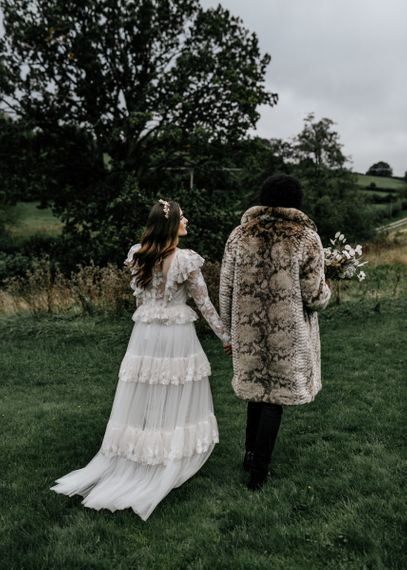 Bride in Tiered Wedding Dress and Groom in Faux Fur Coat Walking Through the Countryside