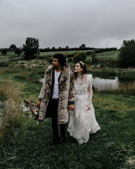 Stylish Bride in Lace KATYA KATYA Wedding Dress with High Neck Detail and Groom in Faux Fur Coat