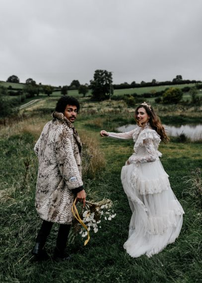 Stylish Bride in Wedding Dress with Long Sleeves and Gold Crown and Groom in Faux Fur Coat
