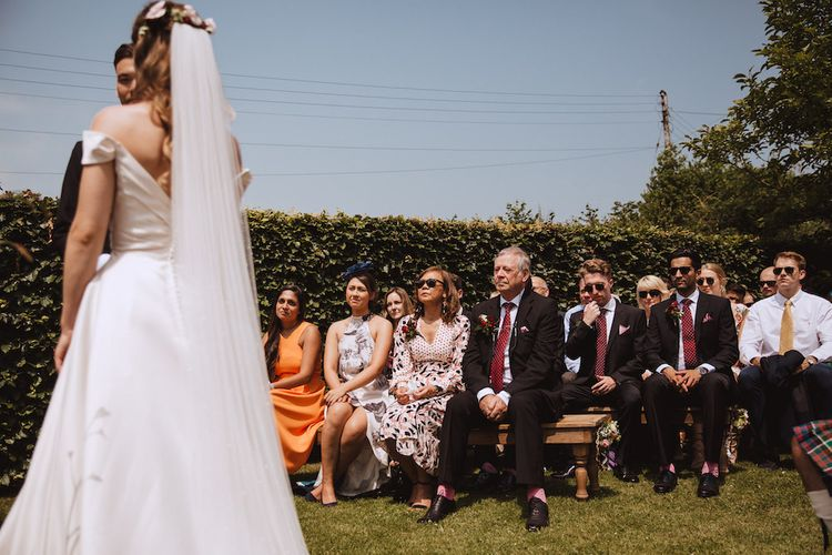 Outdoor Wedding Ceremony with Wedding Guests Sitting on Benches