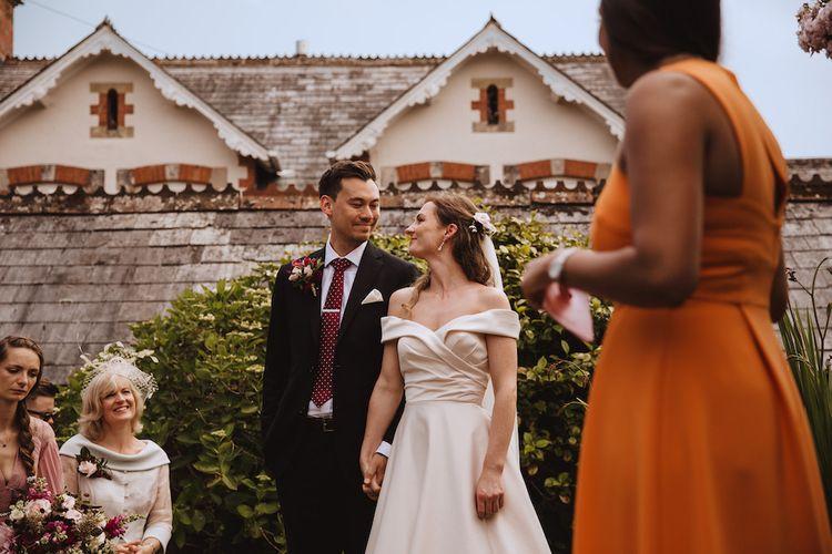 Outdoor Wedding Ceremony with Bride in Bardot Wedding Dress and Groom in Moss Bros. Suit