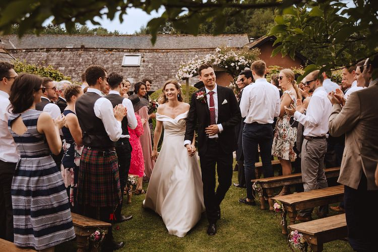 Bride in Bardot Art Couture Wedding Dress and Groom in Black Moss Bros. Suit with Burgundy Tie Walking Up the Aisle as Husband and Wife