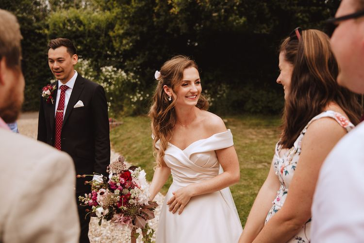 Beautiful Bride with Half Up Half Down Hair Greeting Wedding Guests