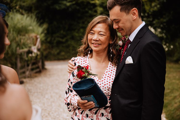 Mother of the Groom and The Groom in Black Moss Bros. Suit and Burgundy Tie Hugging