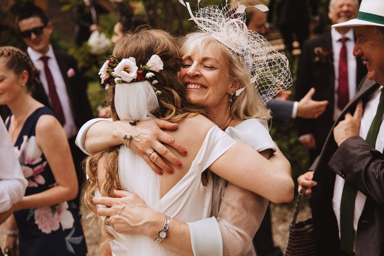 Mother of the Bride in a Birdcage Veil Hugging Her Daughter with Fresh Flowers in Her Hair