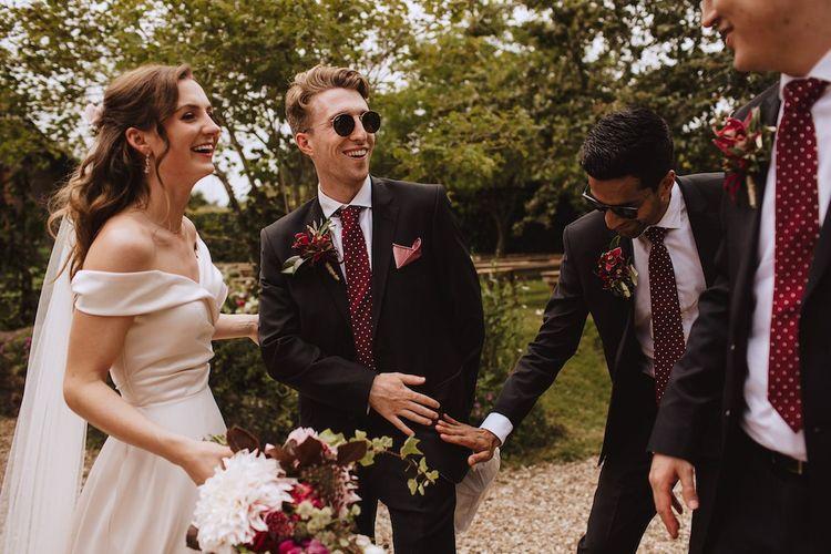 Groomsmen in Black Suits with Burgundy Polka Dot Ties Congratulating The Bride
