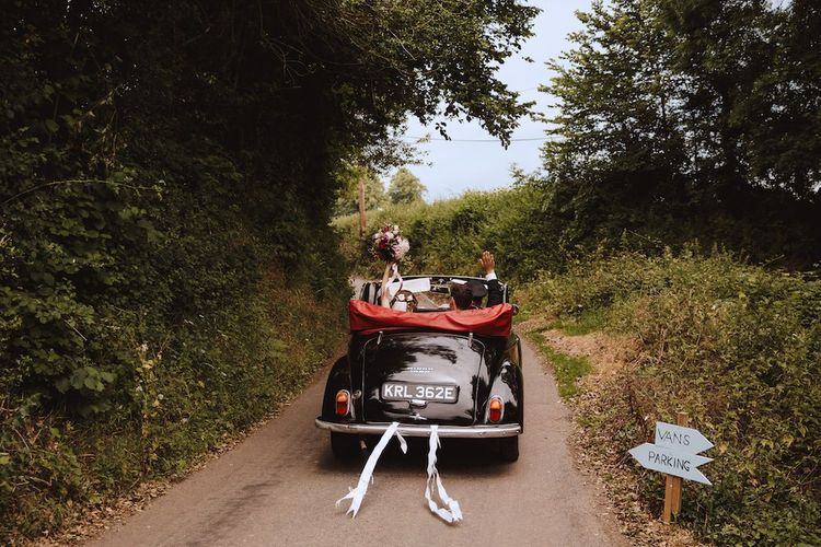 Bride and Groom Driving Off into the Sunset in a Black Vintage Wedding Car