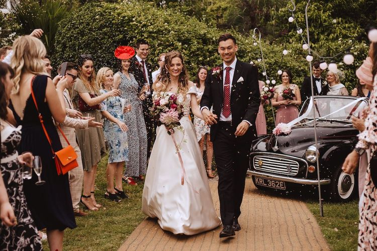Confetti Moment with Bride in Bardot Wedding Dress and Groom in Black Moss Bros. Suit and Burgundy Tie