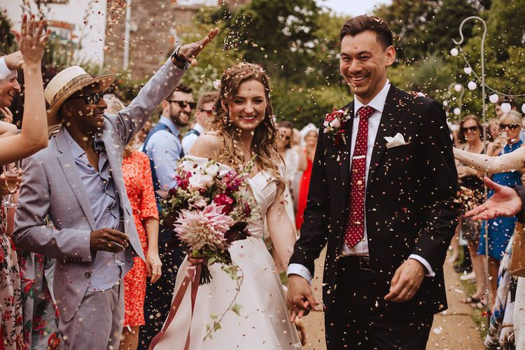 Confetti Exit with Bride in Bardot Wedding Dress and Groom in Black Moss Bros. Suit and Burgundy Tie