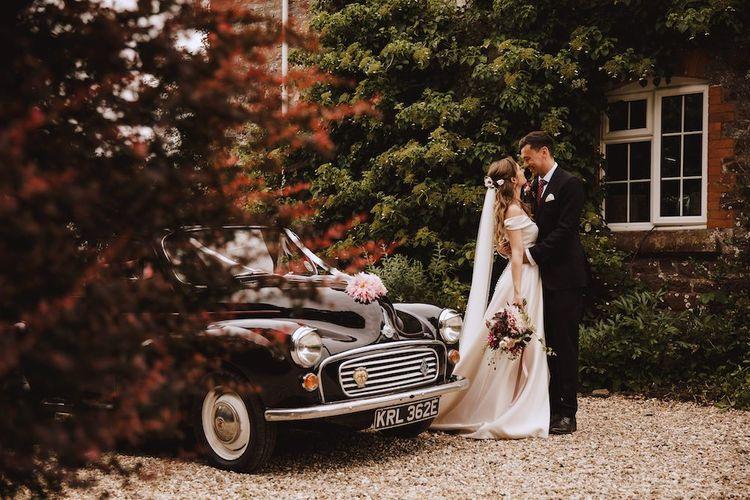 Bride in Bardot Wedding Dress and Groom in Black Moss Bros. Suit and Burgundy Tie Standing Next to their Vintage Black Wedding Car