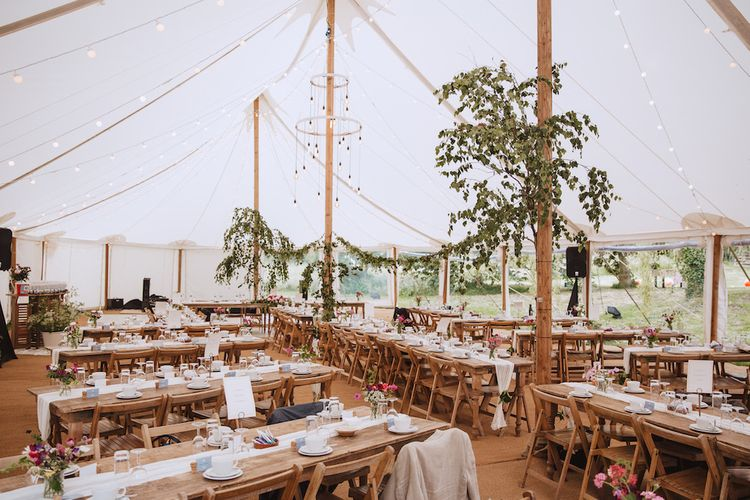 Rustic Tent Wedding Decor with Wooden Tables, Greenery and Festoon Lights