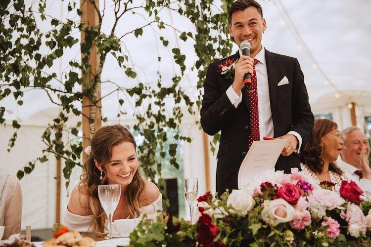 Groom in Black Moss Bros. Suit with Burgundy Tie Giving His Wedding Speech