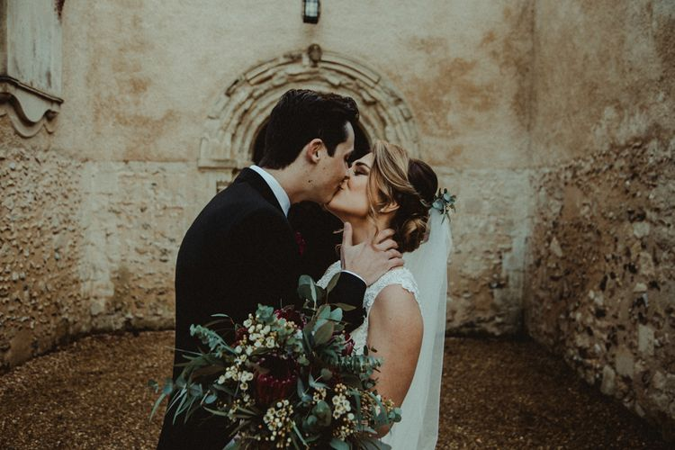 Bride in The Eleni Wed2B Lace Wedding Dress Holding a Protea Bridal Bouquet and Groom in Black Tie Kissing