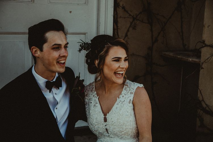 Bride in The Eleni Wed2B Lace Wedding Dress Holding a Protea Bridal Bouquet and Groom in Tuxedo Laughing