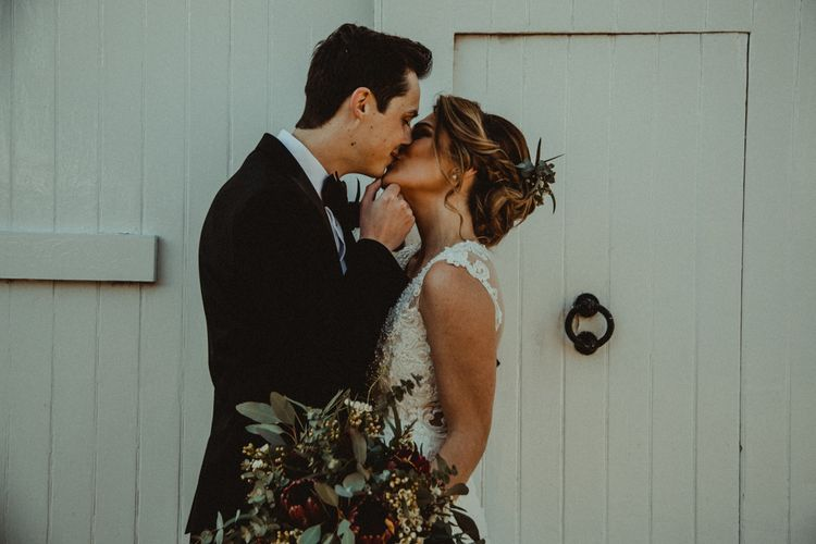Bride in The Eleni Wed2B Lace Wedding Dress Holding a Protea Bridal Bouquet and Groom in Tuxedo Kissing