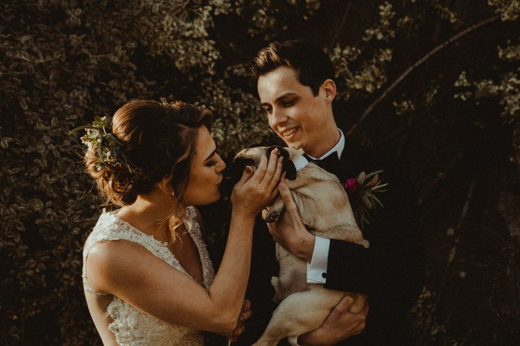 Bride in The Eleni Wed2B Lace Wedding Dress and Groom in Tuxedo with Their Pet Pug