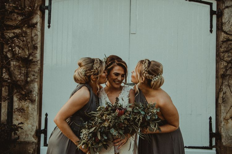 Bride in The Eleni Wed2B Lace Wedding Dress and Bridesmaids in Sage Green One Shoulder Dresses
