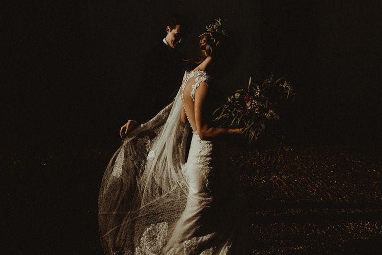 Bride in Lace Wedding Dress and Groom in Black Tie Suit Walking