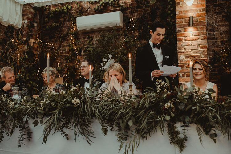 Grooms Wedding Speech at the Top Table with Foliage and Taper Candle Wedding Decor