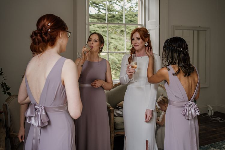 Bridal party on wedding morning sipping champagne