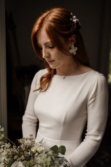 Beautiful bride in Minimalist wedding dress by Alexandra Grecco with long sleeves