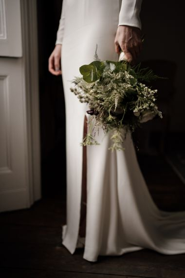 Bride in minimalist wedding dress holding a green and white bouquet