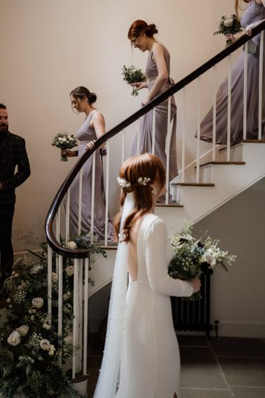 Bridal party walking down the stairs at Aswarby Rectory