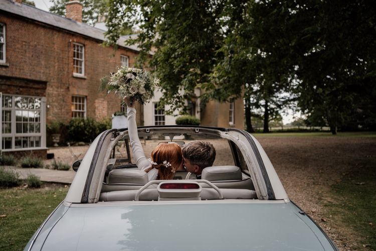 Bride and groom in wedding car at Aswarby Rectory
