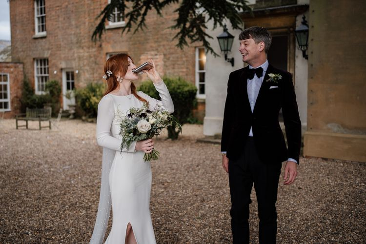 Bride in minimalist Alexandra Grecco wedding dress sipping from the grooms hip flask