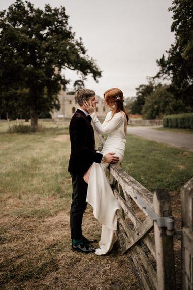 Bride in Alexandra Grecco wedding dress sitting on a gate
