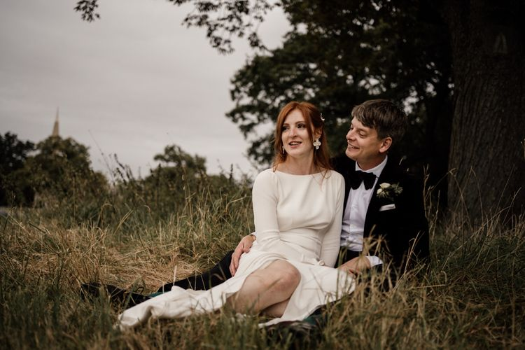 Bride and groom portrait in a field by Magda K Photography