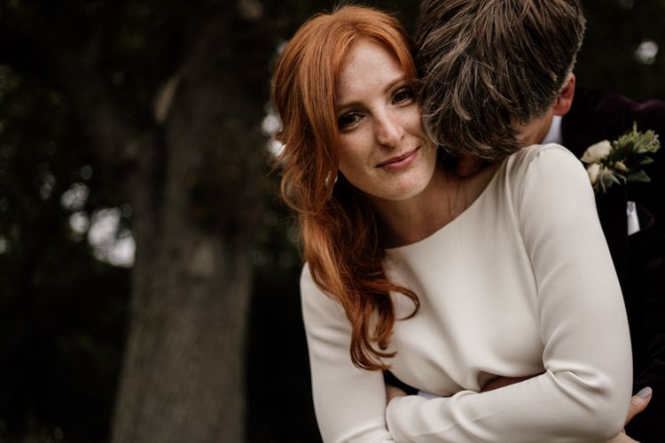 Beautiful bride with red hair and freckles in long sleeve Alexandra Grecco wedding dress