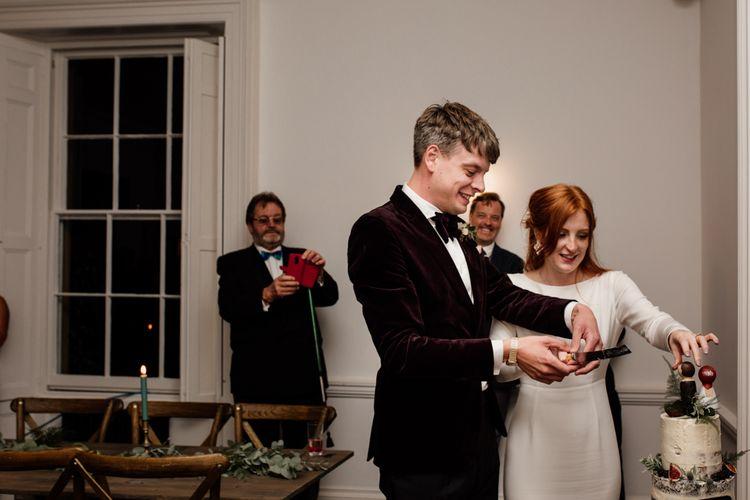 Groom in velvet tuxedo and bride in minimalist wedding dress cutting the wedding cake