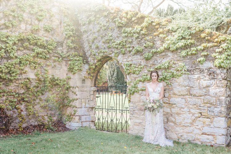 Bride in Stephanie Allin Floral Wedding Dress Standing in Romantic Walled Garden