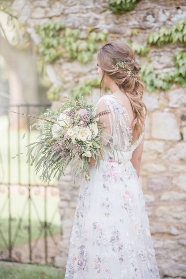 Bride in Stephanie Allin Floral Wedding Dress Holding Romantic White and Lilac Wedding Bouquet with Foliage