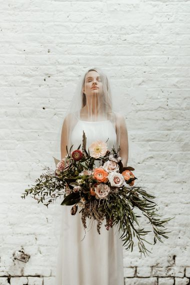 Beautiful Bride in Oversized Bridal Bouquet with Foliage and Peach Flowers