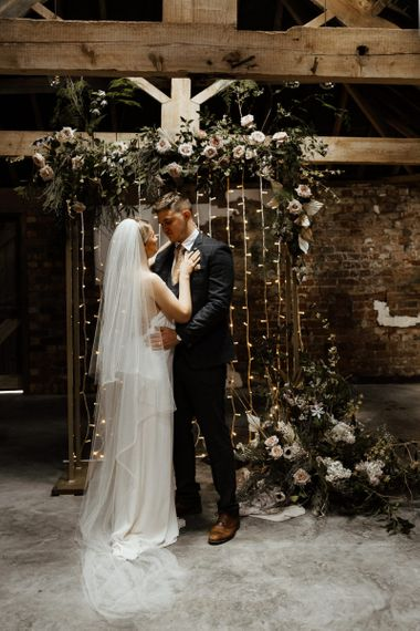 Bride and Groom Embracing at a Flower and Fairy Light Altar