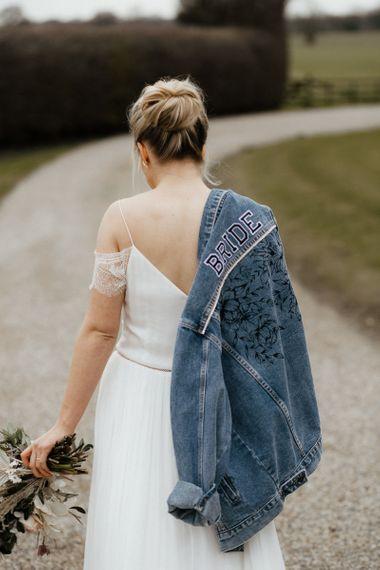 Bride in Spaghetti Strap Wedding Dress and Denim Jacket