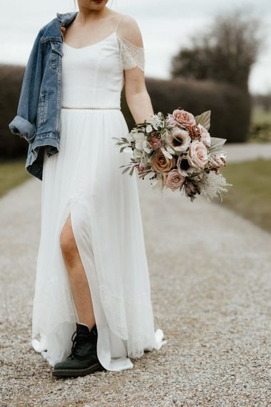 Bride in Spaghetti Strap Wedding Dress with Front Split, Boots and Denim Jacket