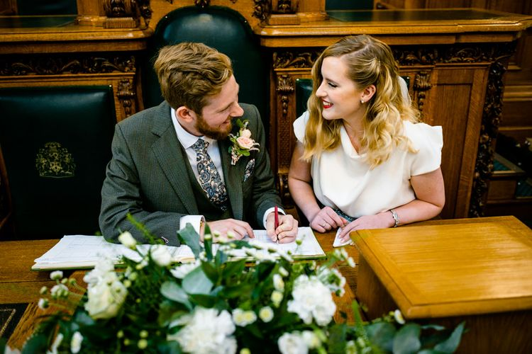 Bride in Vintage Wedding Dress and Groom in Tailored Suit Signing The Register
