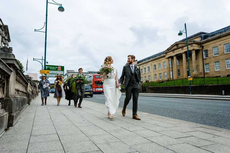 Bride in Vintage Wedding Dress and Groom in Tailored Suit  Walking Through Manchester