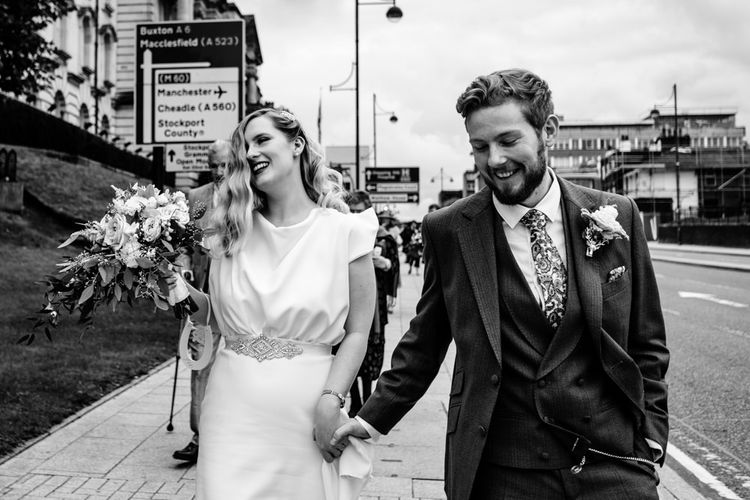 Black and White Portrait of Bride in Vintage Wedding Dress and Groom in Tailored Suit  Walking Through Manchester